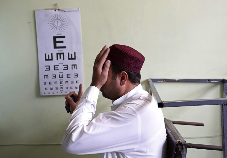 Image: An Afghan man takes an eye test before receiving a driving license at a traffic police department in Kabul