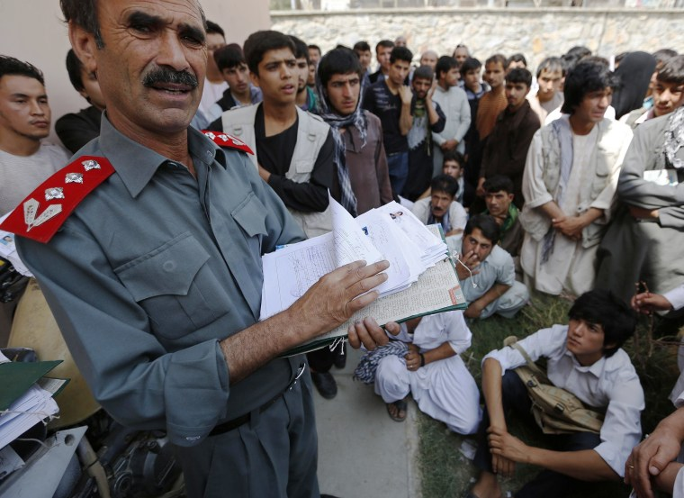 Image: Afghan men wait as an official holds their driving test papers at a traffic police department in Kabul