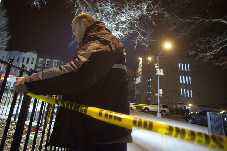 Image: A policeman puts up crime scene tape at scene of shooting where two New York Police officers were shot dead in Brooklyn borough of New York