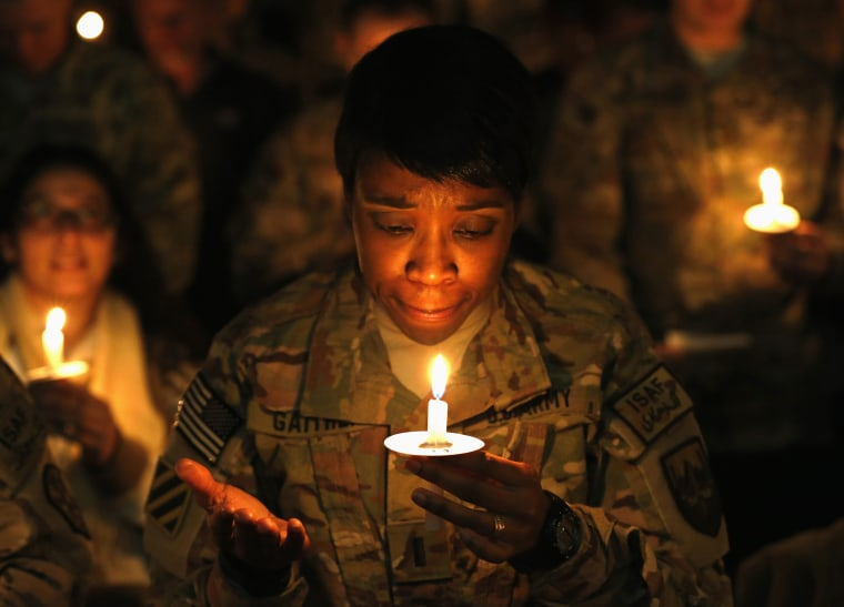 Image: U.S. troops from the Nato-led ISAF light candles during Christmas Eve celebrations at Bagram Airfield, north of Kabul