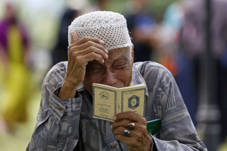Image: An Acehnese man cries while praying for a tsunami victim at a mass graveyard in Banda Aceh