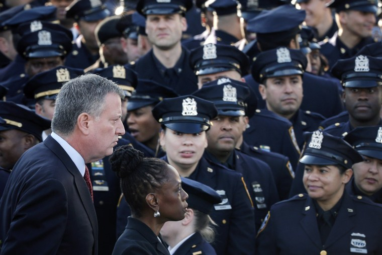 Image: New York Mayor de Blasio and wife Chirlane walk past a sea of policemen while arriving for the funeral services of NYPD officer Ramos in the Queens borough of New York