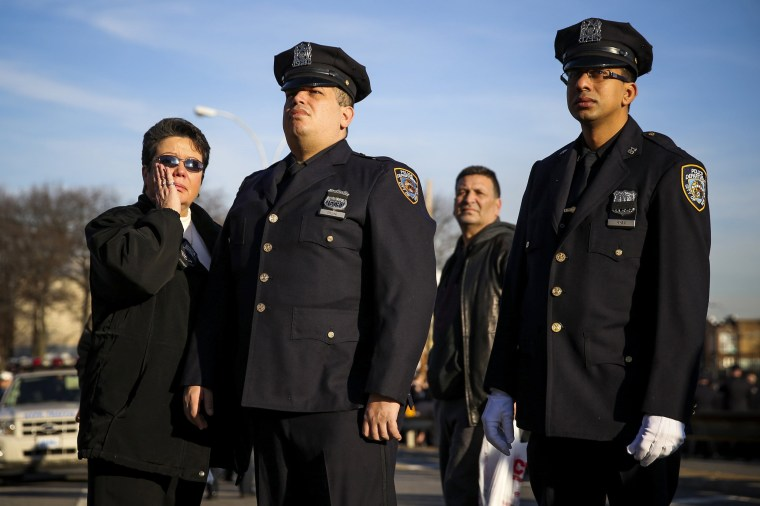 Image: Members of the NYPD watch a tribute video for the funeral of slain NYPD officer Ramos near Christ Tabernacle Church in the Queens borough of New York