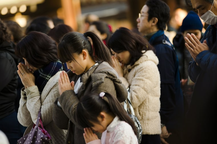 Image: People pray during ceremonies bidding farewell to 2014, ahead of New Year's Day, at the Meiji Shrine in Tokyo