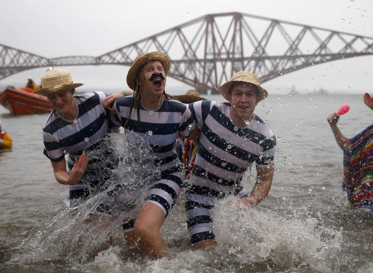 Image: Swimmers in fancy dress splash as they participate in the New Year's Day Loony Dook swim at South Queensferry, Scotland