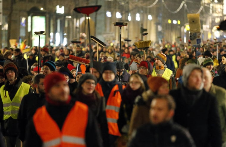 Image: Participants of an alternative rally carry brooms as they protest against a demonstration called by anti-immigration group PEGIDA in Dresden