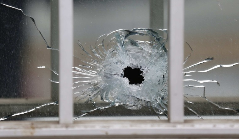 Image: A bullet's impact is seen on a window at the scene after a shooting at the Paris offices of Charlie Hebdo, a satirical newspaper,