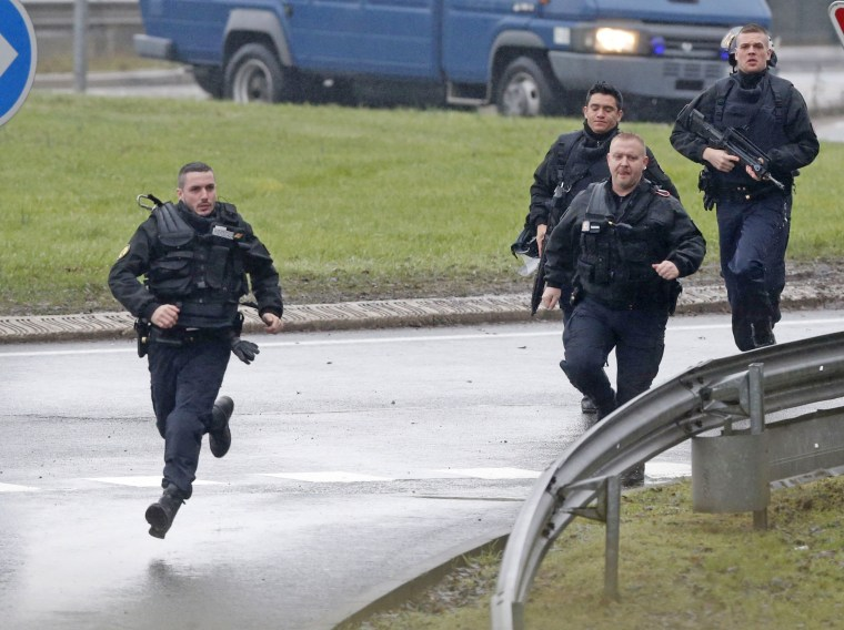Image: Members of the French gendarmerie intervention forces arrive at the scene of a hostage taking at an industrial zone in Dammartin-en-Goele, northeast of Paris