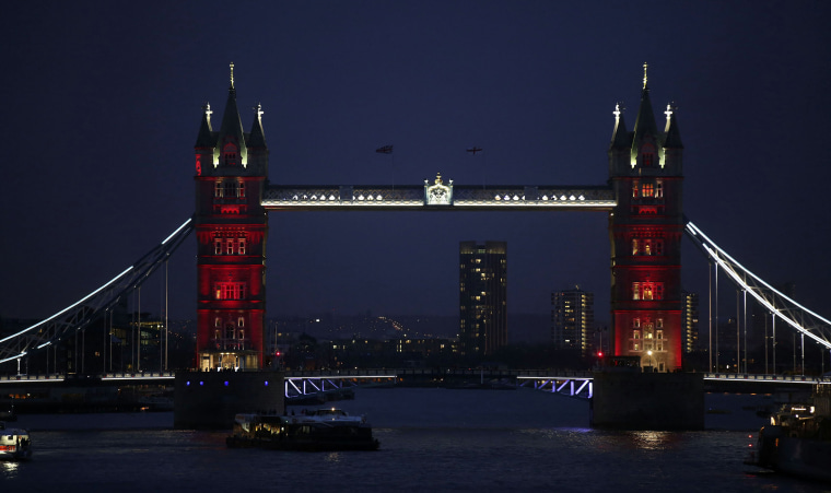Image: Tower Bridge is seen lit in the colours of the French national flag in a tribute to the 17 people killed in the Paris terror attacks, in London