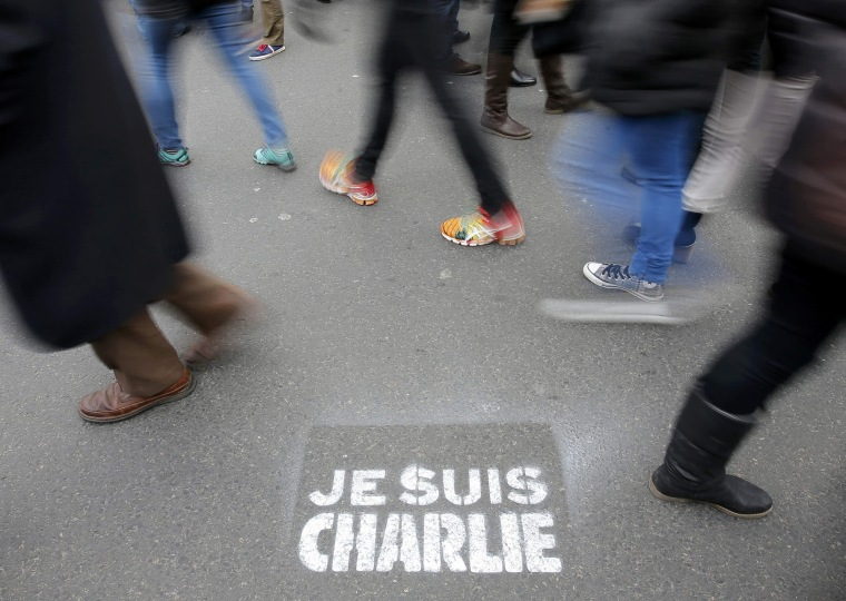 "Image: People walk past a grafitti tag reading ""I am Charlie"" as they take part in a solidarity march (Marche Republicaine) in the streets of Paris"