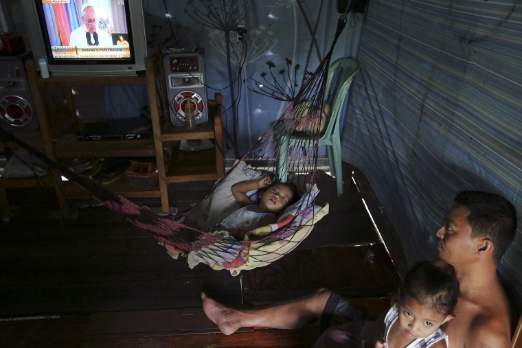 Image: A baby sleeps as other family members watch live coverage of Pope Francis' visit to Manila, in the coastal part of Tacloban