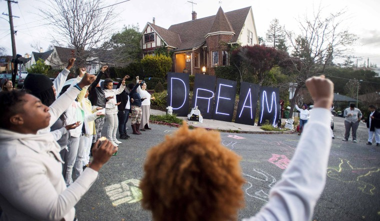 """Image: Black rights protesters gather near illuminated letters spelling """"DREAM"""" outside a house which they identified as the residence of Oakland Mayor Libby Schaaf, in Oakland"""