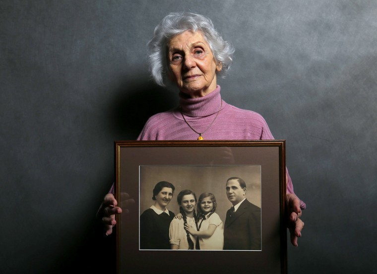 Image: Auschwitz death camp survivor Eva Fahidi holds a picture of her family, who were all killed in the concentration camp during World War II