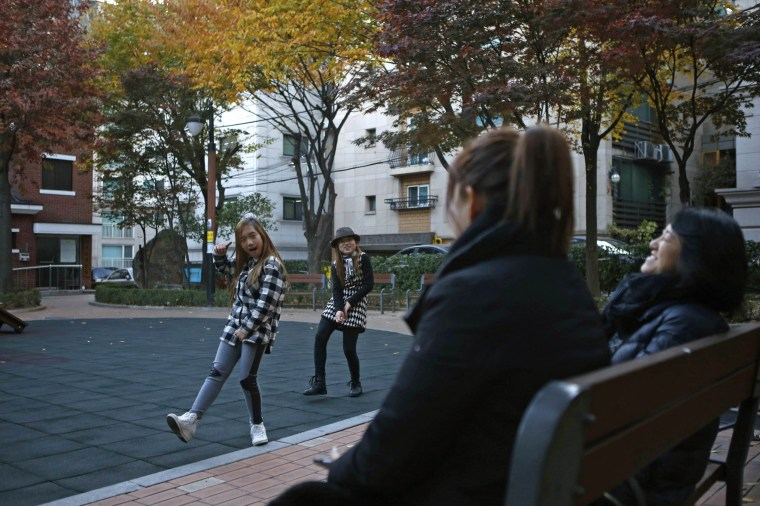 Image: Kim Si-yoon and Yoo Ga-eul dance in front of their mothers at a playground in Seoul