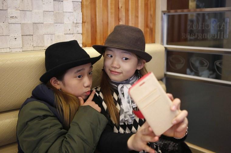 Image: Kim Si-yoon and Yoo Ga-eul take a selfie at a restaurant in Seoul