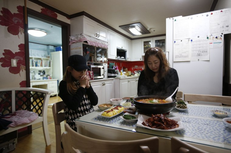 Image: Kim Si-yoon and her mother pray before dinner at their house in Seoul