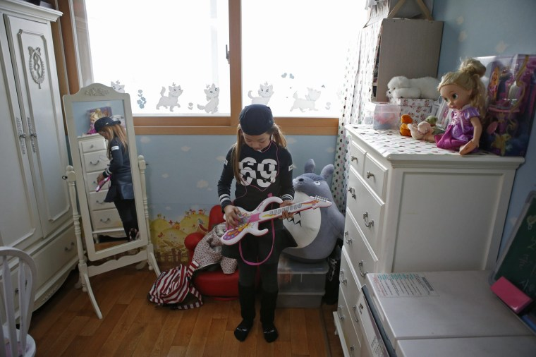 Image: Kim Si-yoon plays a toy guitar at her house in Seoul