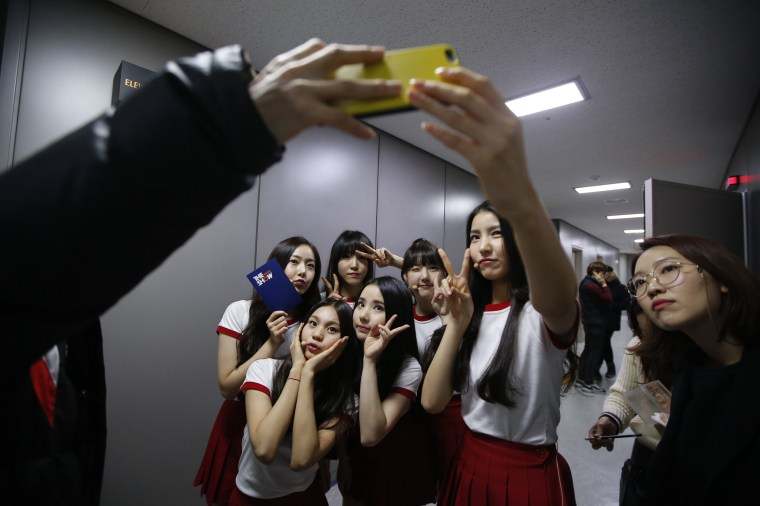 """Image: Members of South Korean girl group GFriend take a 'selfie' after their performance in """"The Show"""" in Seoul"""