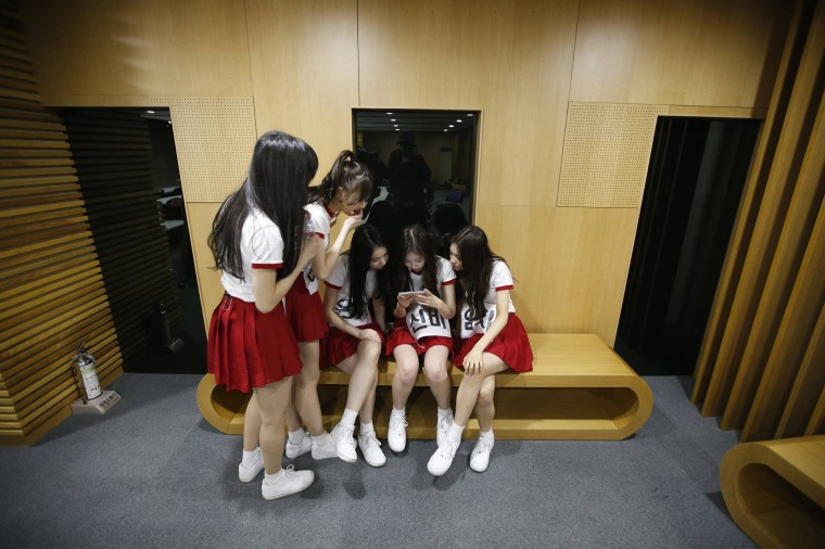 Image: Members of South Korean girl group GFriend watch a recording of their stage performance during a dress rehearsal for The Show in Seoul