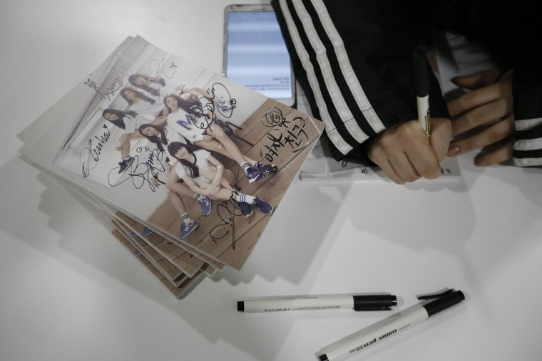 """Image: A member of South Korean girl group GFriend signs her autograph on their album as they rest before """"The Show"""" in Seoul"""