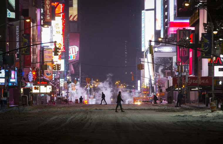 Image: People cross a car-free snow covered seventh avenue in midtown Manhattan in New York City