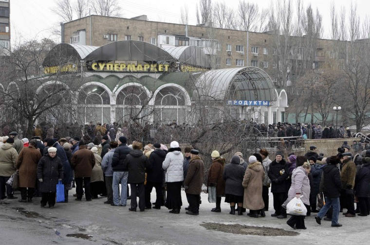 Image: Local residents wait in a queue to get humanitarian aid near a grocery store in Donetsk