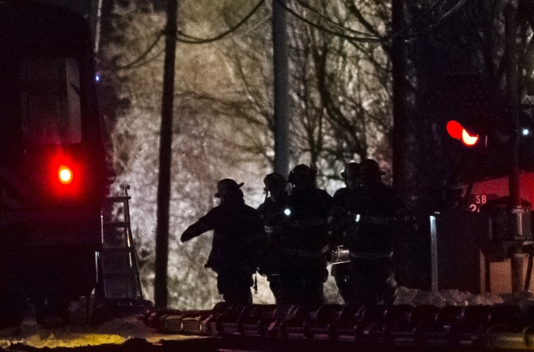 Image: Firefighters carry a stretcher over railroad tracks at the site of an accident involving a commuter train in Mount Pleasant, near Valhalla, New York