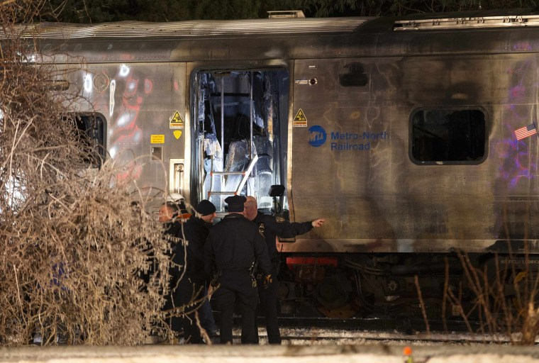 Image: Emergency workers stand near a burned out Metropolitan Transportation Authority Metro North Railroad commuter train near the town of Valhalla, New York
