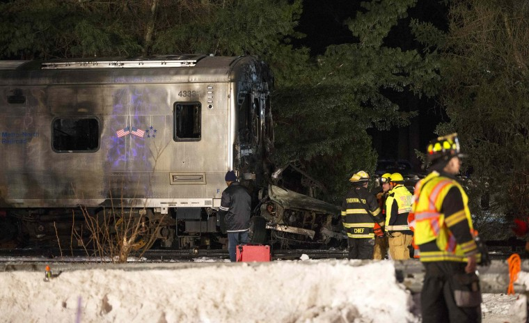 Image: Emergency workers stand near burnt Metropolitan Transportation Authority Metro North Railroad commuter train near the town of Valhalla, New York
