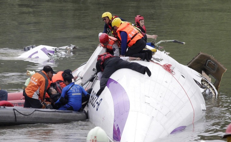 Image: Rescuers pull a passenger out of the TransAsia Airways plane which crash landed in a river in New Taipei City