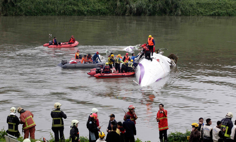 Image: Rescuers carry out rescue operation after a TransAsia Airways plane crash landed in a river, in New Taipei City