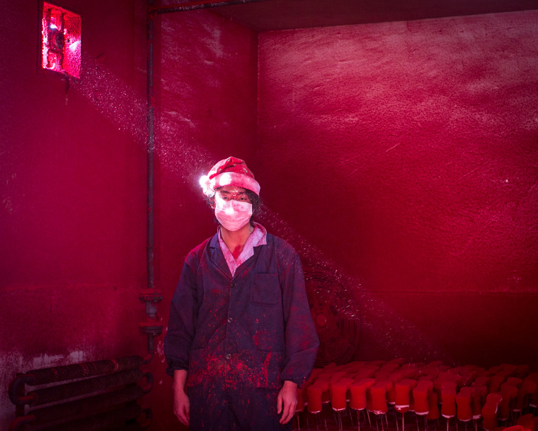 Second Prize Contemporary Issues Wei, a 19-year-old Chinese worker, wearing a face mask and a Santa hat, stands next to Christmas decorations being dried in a factory as red powder used for coloring hovers in the air in Yiwu, China. He wears six masks a day and the hat protects his hair from the red dust, which covers workers from head to toe like soot after several hours of work.