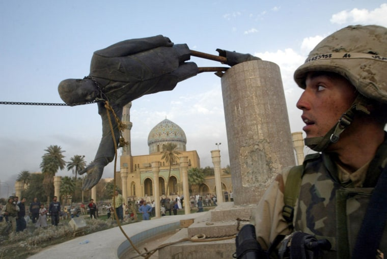 Image: File photo of U.S. Marine Corp Assaultman Kirk Dalrymple watching as a statue of Iraq's President Saddam Hussein falls in central Baghdad