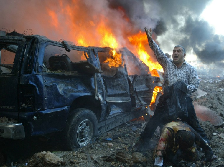 Image: File photo of a Lebanese man shouting for help for a wounded man near the site of a car bomb explosion in Beirut