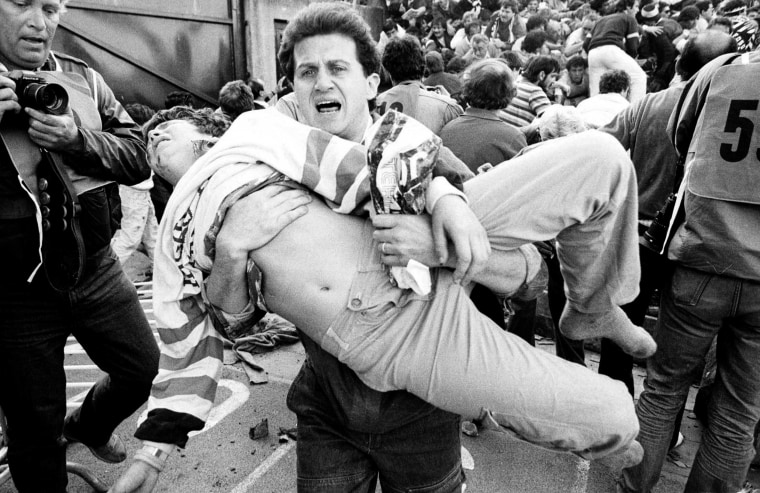 Image: File photo of an injured soccer fan being carried to safety by a friend after a wall collapsed during violent rioting before the European Cup final between Juventus and Liverpool