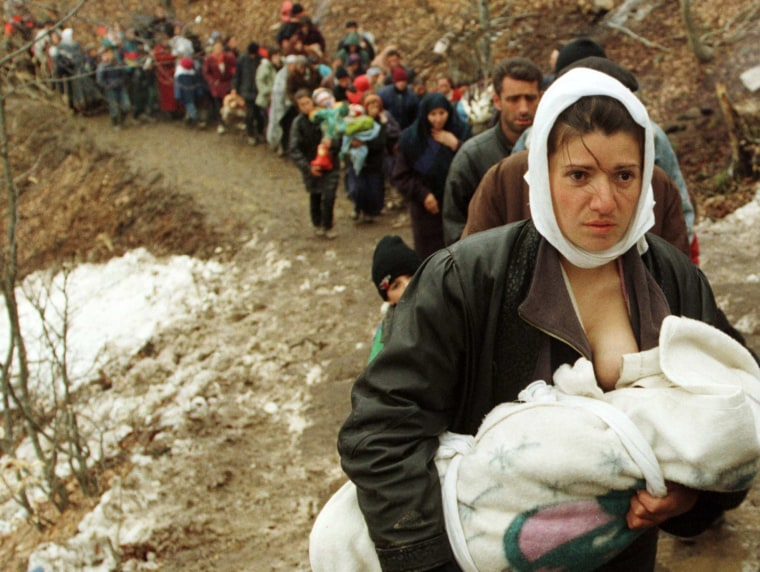Image: File photo of an ethnic Albanian woman feeding her baby as she and another 2,000 refugees walk up a muddy dirt track after they were allowed to enter Macedonia