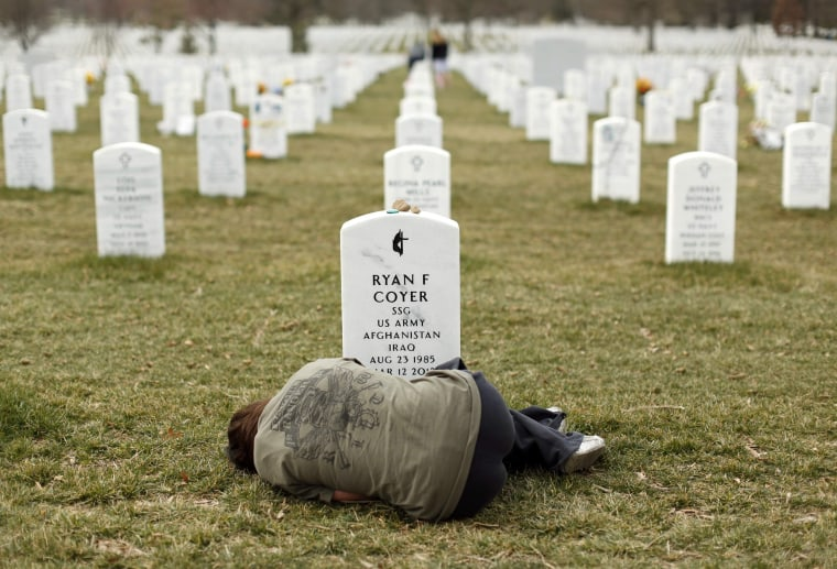 Image: File photo of a woman lying down in front of the grave of her brother at Arlington National Cemetery near Washington