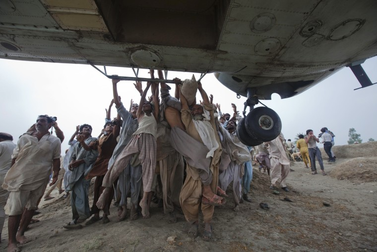 Image: File photo of Marooned flood victims trying to grab the side bars of a hovering Army helicopter which arrived to distribute food supplies in the Muzaffargarh district of Pakistan's Punjab province