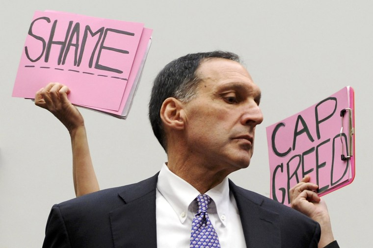 Image: File photo of protestors holding signs behind Fuld as he takes his seat to testify at a House Oversight and Government Reform Committee