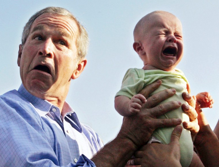 Image: File photo of US President Bush handing back a crying baby that was handed to him in Trinwillershagen