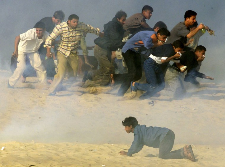 Image: File photo of Palestinians trying to run away from Israeli soldiers firing teargas