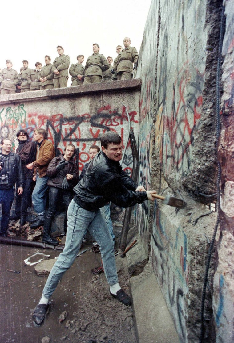 Image: File photo of a demonstrator pounding away at the Berlin Wall as East Berlin border guards look on from above the Brandenburg Gate