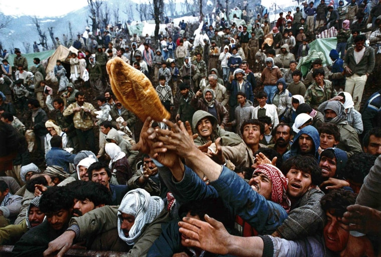 Image: File photo of frantic Kurdish refugees struggling for a loaf of bread during a humanitarian aid distribution for hundreds of thousands of stranded Iraqi-Kurds in the mountains of Isikveren at the Iraqi-Turkish border