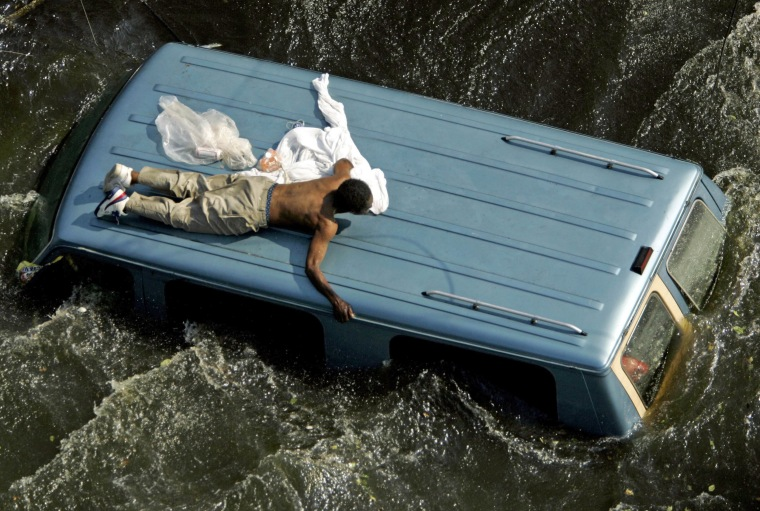 Image: File photo of a man clinging to the top of a vehicle in the aftermath of Hurricane Katrina in New Orleans