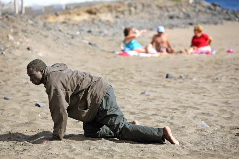 Image: File photo of  a would-be immigrant crawling on a beach after his arrival in Fuerteventura