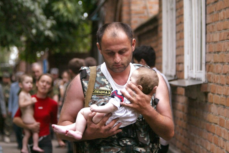 Image: File photo of a Russian police officer carrying a released baby from Beslan school