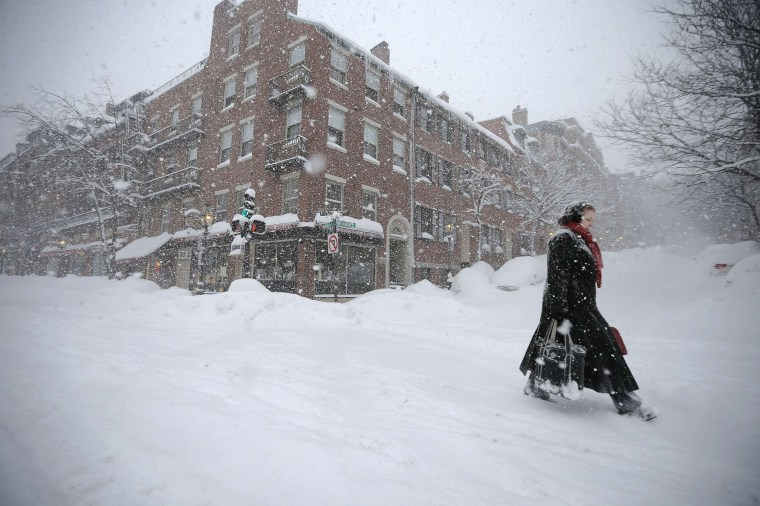 Image: A woman walks through the snow down Charles Street during a winter blizzard in Boston