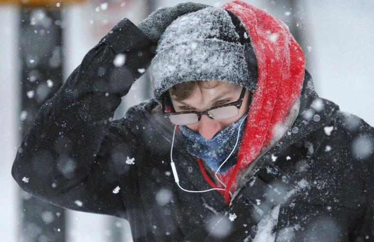 Image: A pedestrian walks through the snow during a winter blizzard in Cambridge
