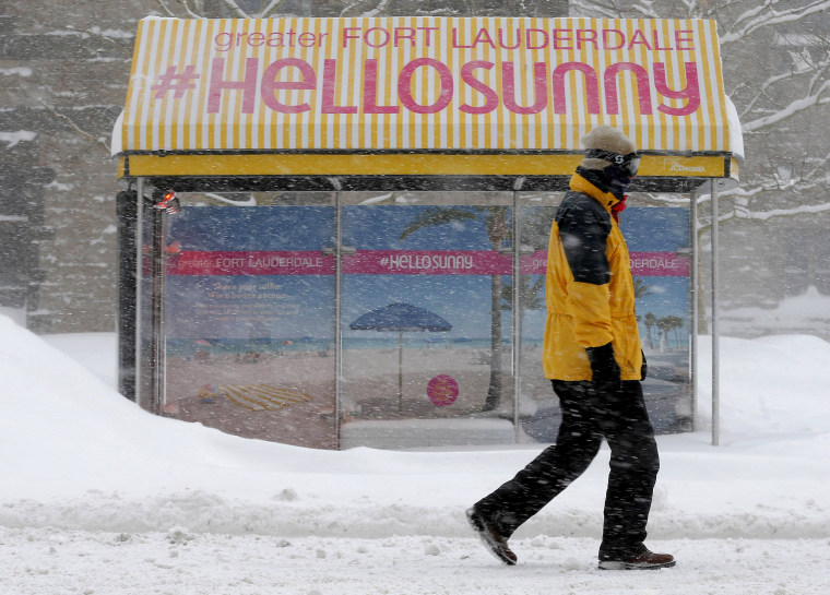 Image: Pedestrian walks past a bus stop with an advertisement for Florida during a winter blizzard in Boston