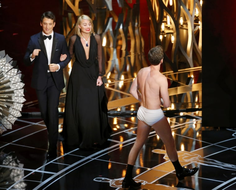 Image: Neil Patrick Harris walks offstage in his underwear as Miles Teller and Margot Robbie walk on to present the Scientific and Technical awards at the 87th Academy Awards in Hollywood, California